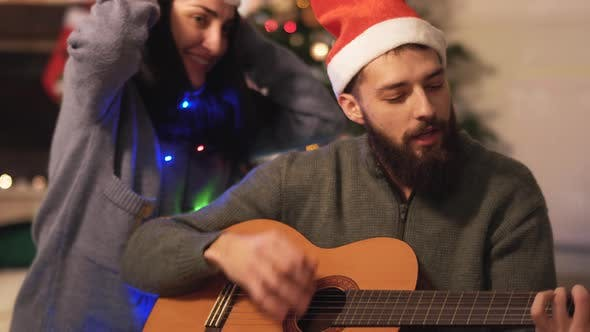 Thumbnail for Man Playing Guitar and Singing Sitting on the Floor Near Christmas Tree in Modern Room. Happy Couple