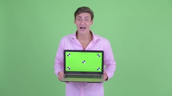 Thumbnail for Happy Young Handsome Businessman Showing Laptop and Looking Surprised