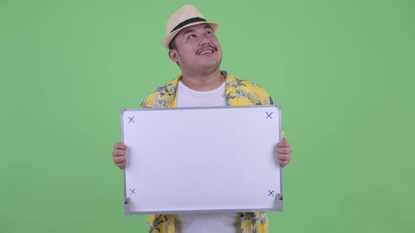 Thumbnail for Happy Young Overweight Asian Tourist Man Thinking While Holding White Board