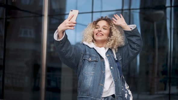 Thumbnail for Curly Girl Makes a Video Call and Waving a Hand Friendly at the Cell Phone Camera.