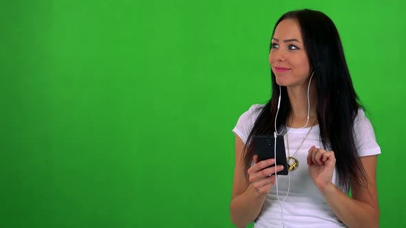 Thumbnail for Young Pretty Woman Listens Music with Earphone on Smartphone - Green Screen - Studio