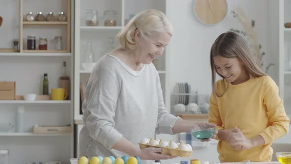 Thumbnail for Senior Woman and Young Granddaughter Preparing to Dye Easter Eggs