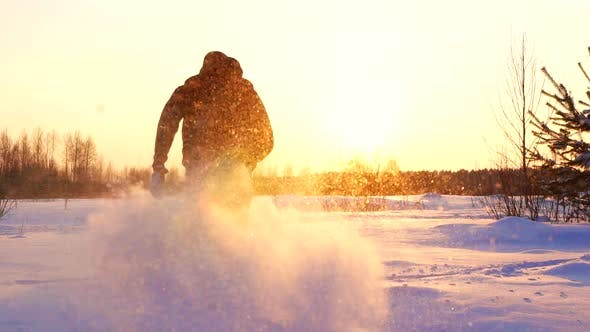 Silhouetted Man Running Through Snow in Winter Landscape