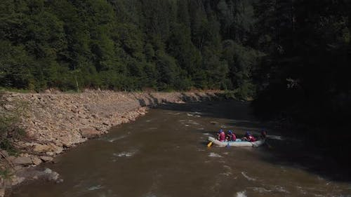 Aerial View of People Floating in Boat on Mountain River
