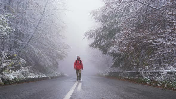 Thumbnail for Confident Young Tourist Walks on Asphalt Road Trough Frozen Forest in the Mountains