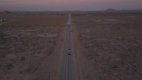 Thumbnail for AERIAL: Flight Over Lonely Abandoned Desert Road with Red Car Driving in the Distance