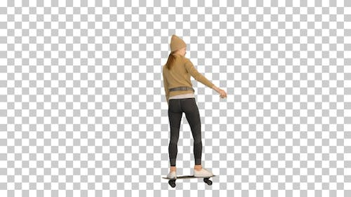 Sporty woman in warm clothes skateboarding by, Alpha Channel