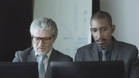 Diverse Male Office Colleagues Working at Workplaces
