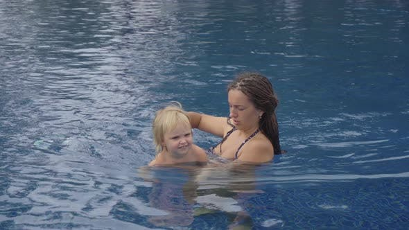 Thumbnail for Mom with a Two-year-old Daughter in Hotel Pool Near Ocean