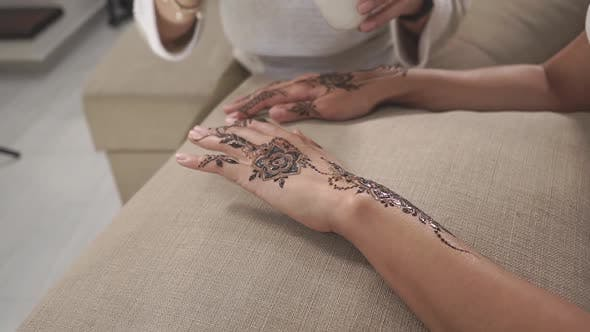 Master Is Covering Dried Mehendi Patterns By Natural Oils for Moisturizing