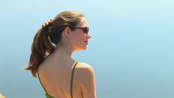 Thumbnail for Head and shoulder portrait of young woman in swimsuit enjoying the sun