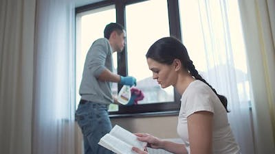 Husband Cleans the Window and Wife Reading the Book