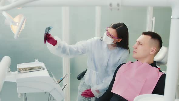 The Doctor Together with the Patient Examines the Xray of the Teeth in the Dental Clinic