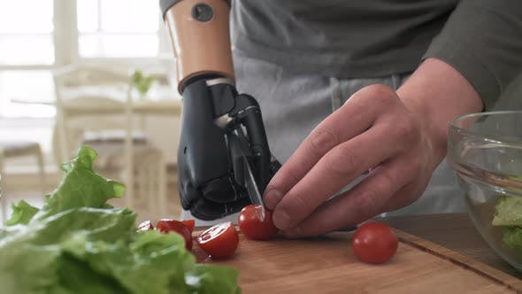 Thumbnail for Handicapped Man with Bionic Forearm Cutting Cherry Tomatoes