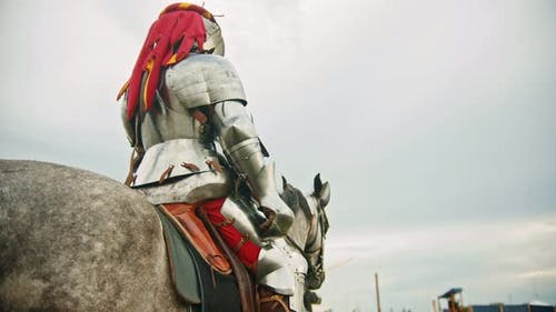 A Man Knight in Helmet with Fabric Clippings Riding a Horse on the Battlefield