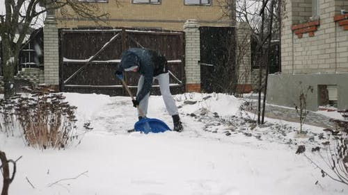 Man is shoveling snow in backyard in snow storm