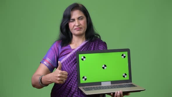 Thumbnail for Mature Beautiful Indian Woman Showing Laptop and Giving Thumbs Up