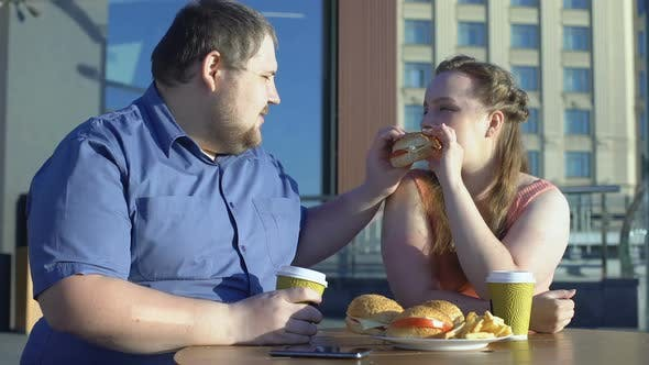 Thumbnail for Happy Woman Enjoying Burger Taste, Fat Couple Eating Fast Food in Cafe Outdoors