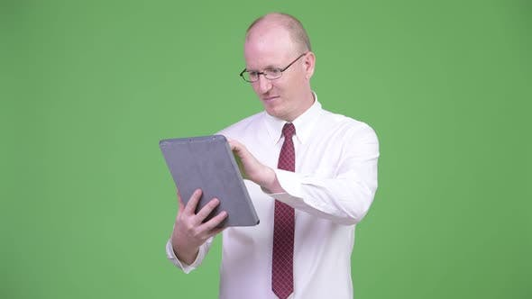 Thumbnail for Happy Mature Bald Businessman Using Digital Tablet and Looking Shocked