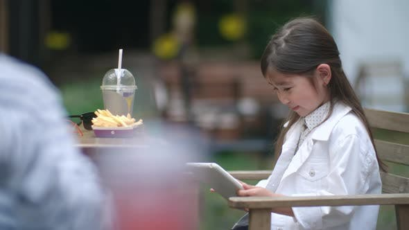 Cover Image for Joyous Little Girl Playing on Digital Tablet in Outdoor Cafe
