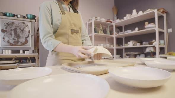 Thumbnail for Female Artisan Sanding Handmade Clay Plate