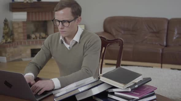 Cover Image for Portrait Young Modestly Dressed Man in Glasses Sitting at the Wooden Table in the Office Working