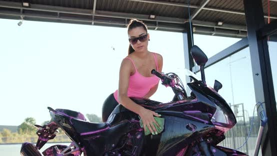 Thumbnail for Female Motorcyclist in Sunglasses and Pink Top Wiping Sporty Black Motorbike