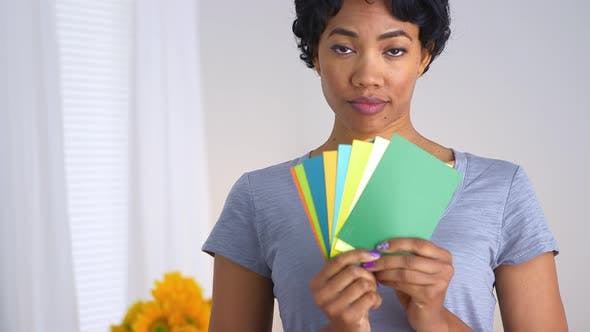 Thumbnail for African American woman holding up fan of paint chips