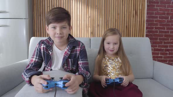 Thumbnail for Cute Caucasian Children Sitting on Sofa and Playing Video Game. Boy Loosing, Girl Making Victory