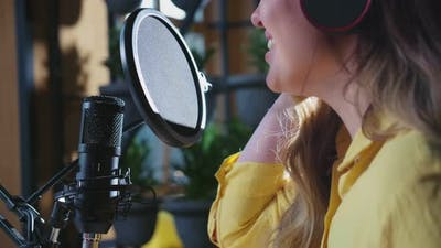 Young Cute Woman Singing Into Microphone