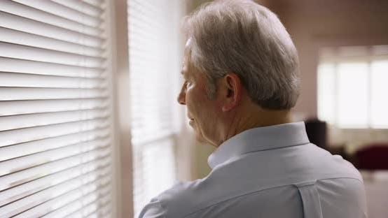 Thumbnail for Closeup of mature Caucasian man looking through window blinds