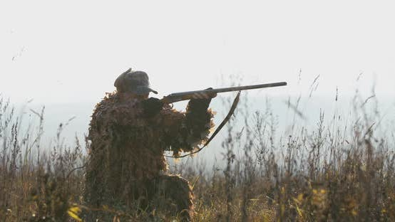 Thumbnail for Hunter lies in wait in the field. A man in hunting equipment in sunset light find the target