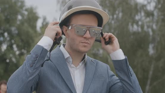 Thumbnail for Close-up of Confident Handsome Man in Sunglasses Putting on Biking Helmet Under Rain. Portrait of