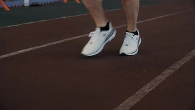 Low Section of Man in Sneakers Jogging on Stadium