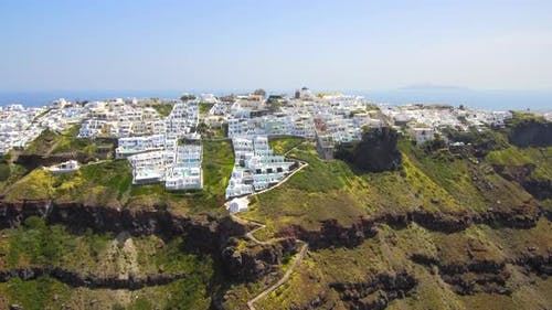 Santorini cliffs with white cave hotels aerial view