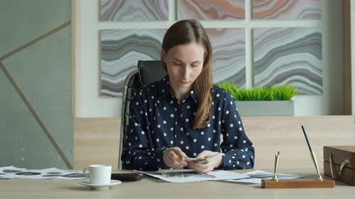 Business Woman in a Shirt Counts Money Sitting at a Desk in the Office