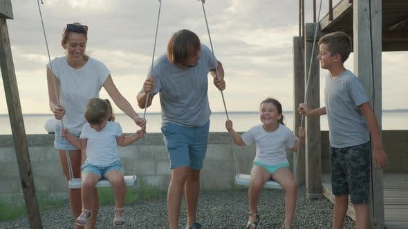 Thumbnail for Big Cheerful Family Having Fun on a Swing.