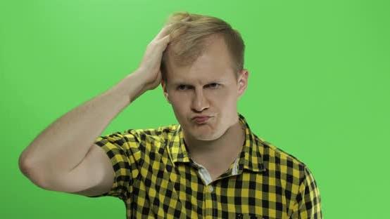 Thumbnail for Hübscher nachdenklicher Mann in gelbem Hemd Blick in die Kamera und denkt