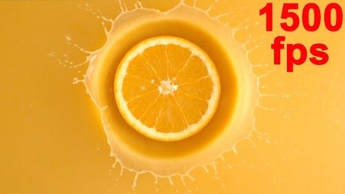 Slice Of Fresh Orange Fruit Falling Into The Juice
