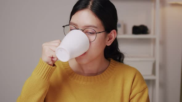Young Asian female having a cup of coffee in the home office.