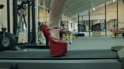 Jeune fille athlétique athlétique effectue un exercice sur un tapis roulant