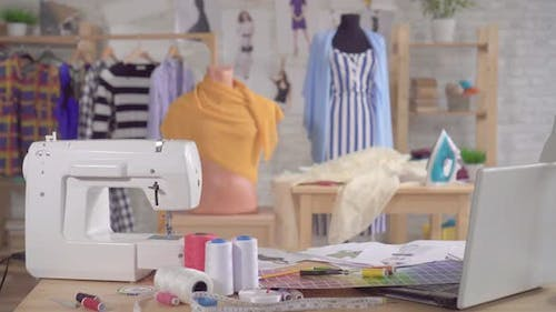 Sewing Machine and Sewing Supplies on the Table in the Studio of a Fashion Designer