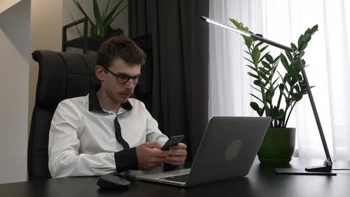 Young confident smart businessman is using smartphone sitting in his modern office desk.
