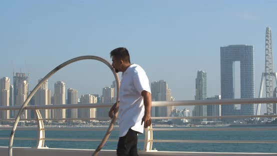 Wheel Gymnast is Leaning on the Railing Ain Dubai in the Background
