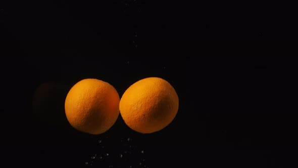 Thumbnail for Oranges Falling Into Water with Bubbles on Black Background. Сitrus Falling Into Water. Slow Motion
