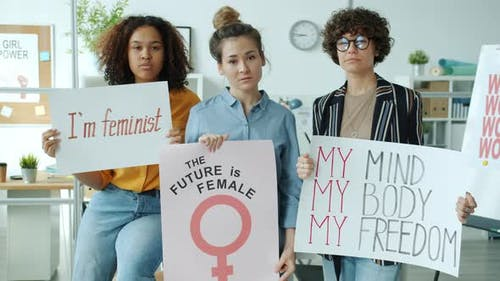 Multiethnic Group of Young Caucasian Asian and AfroAmerican Standing with Feminist Posters Indoors