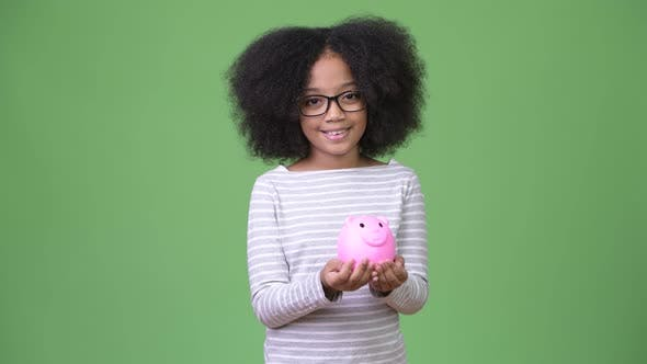 Thumbnail for Young Cute African Girl with Afro Hair Holding Piggy Bank