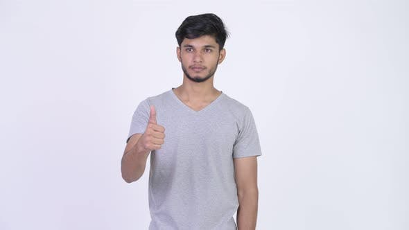 Cover Image for Young Handsome Bearded Indian Man Giving Thumbs Up