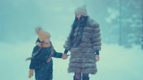 Cheerful Girl with Her Mother Walk in the Winter in the Snow