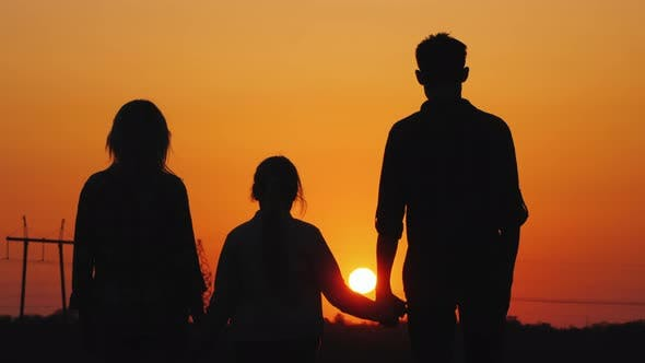 Cover Image for Family of Three Admiring the Orange Sunset Over the City, Rear View